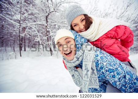 Portrait of happy young couple having fun in winter park - stock photo