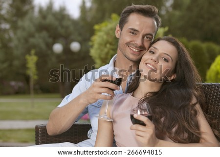 Portrait of happy young couple having red wine together in park - stock photo