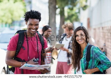 Portrait of happy young couple holding map - stock photo