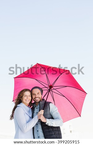 Portrait of happy young couple holding pink umbrella together - stock photo