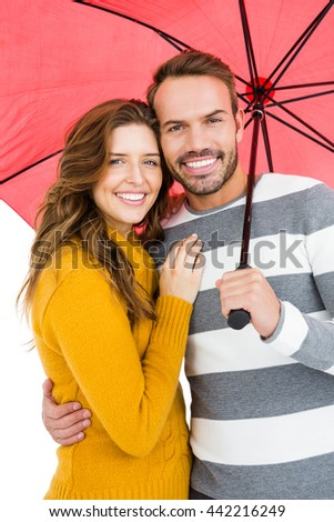 Portrait of happy young couple holding pink umbrella together on white background - stock photo