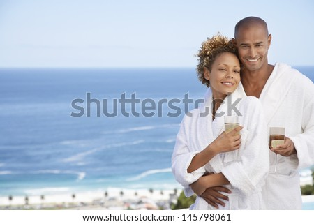Portrait of happy young couple in bathrobes holding drinks with ocean in background - stock photo