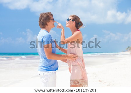 portrait of happy young couple in sunglasses in bright clothes flirting on tropical beach