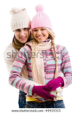 Portrait of happy young couple in warm clothes over white background