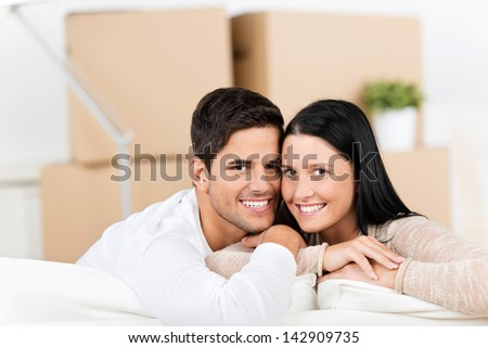 Portrait of happy young couple leaning on sofa with cardboard boxes in background - stock photo