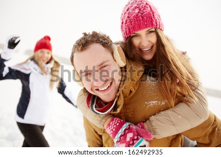 Portrait of happy young couple looking at camera in winter park with their friend behind - stock photo