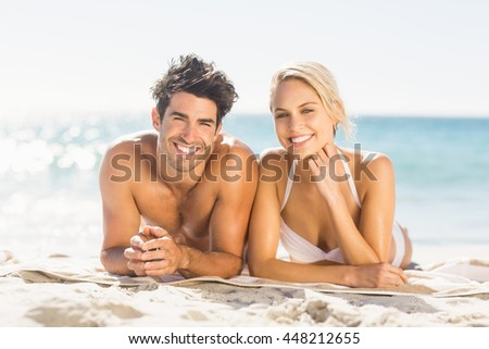 Portrait of happy young couple lying on beach