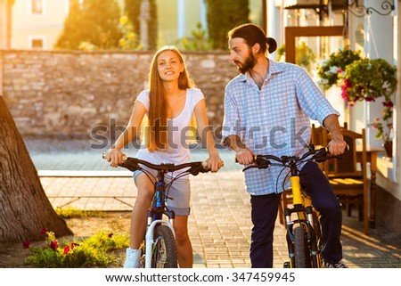 Portrait of happy young couple of bicyclists talking in the street - stock photo