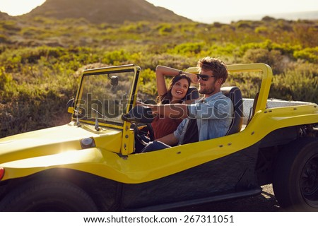 Portrait of happy young couple on a road trip in a beach buggy. Smiling young woman with her boyfriend driving car in countryside. - stock photo
