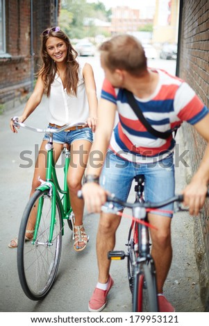 Portrait of happy young couple on bicycles between two houses - stock photo