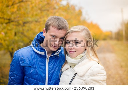 portrait of happy young couple on outdoors cold autumn day - stock photo