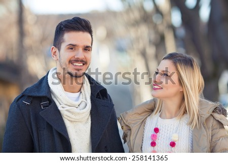 Portrait of happy young couple on the street. Young man is looking at camera, and girl is looking at her boyfriend. - stock photo