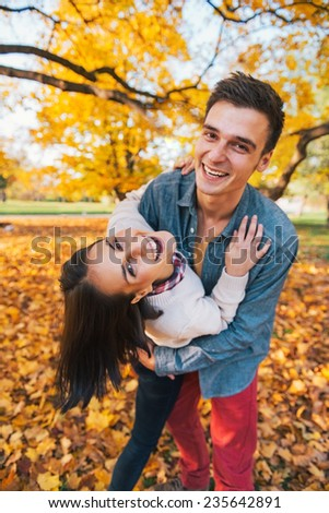 Portrait of happy young couple outdoors in park in autumn having fun time - stock photo