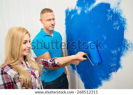 Portrait Of Happy Young Couple Painting Wall With Paint Roller - stock photo