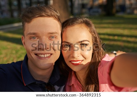 Portrait of happy young couple posing for selfie