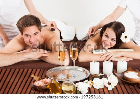 Portrait of happy young couple receiving shoulder massage at beauty spa - stock photo