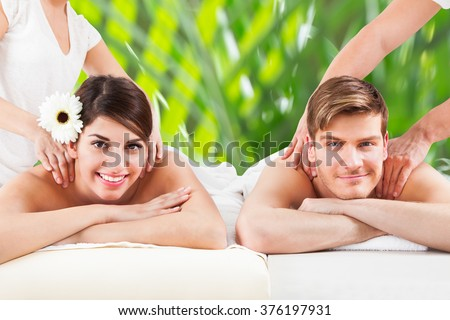 Portrait of happy young couple receiving shoulder massage at spa - stock photo