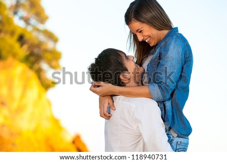 Portrait of happy young couple showing affection outdoors. - stock photo