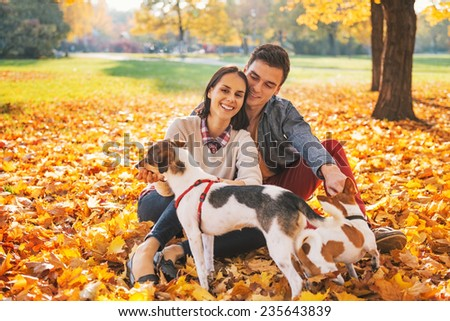 Portrait of happy young couple sitting outdoors in autumn park and playing with dogs - stock photo