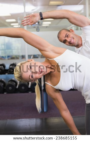 Portrait of happy young couple stretching hands in yoga class - stock photo