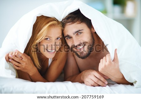 Portrait of happy young couple under blanket looking at camera - stock photo