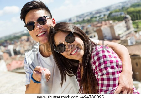 Portrait of happy young couple using mobile phone in the city.