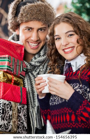 Portrait of happy young couple with disposable cups and Christmas presents standing at store - stock photo