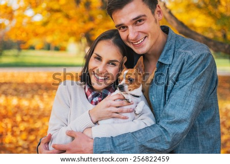 Portrait of happy young couple with dog outdoors in autumn - stock photo
