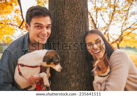 Portrait of happy young couple with dogs outdoors in autumn park - stock photo