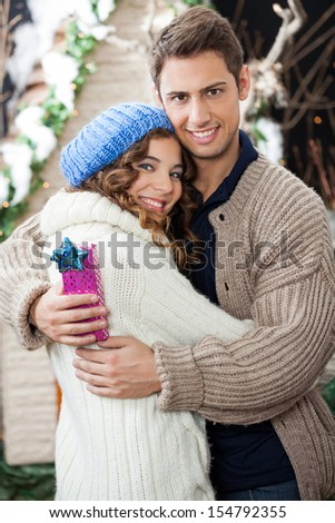 Portrait of happy young couple with gift box embracing at Christmas store - stock photo