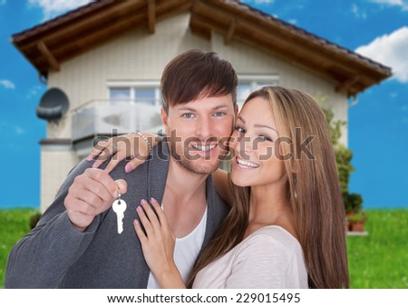Portrait of happy young couple with key against new home - stock photo
