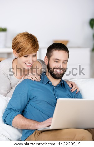 Portrait of happy young couple with laptop in house