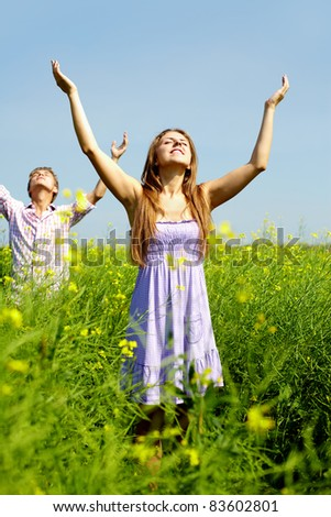 Portrait of happy young couple with raised arms standing in flower field - stock photo