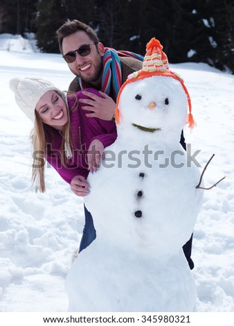 portrait of happy young couple with snowman at beautiful winter day with fresh snow and forest in background - stock photo
