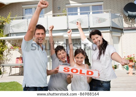 Portrait of happy young family celebrating buying their new house - stock photo