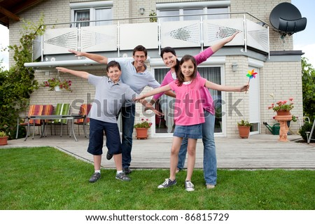 Portrait of happy young family enjoying themselves outside their new home - stock photo