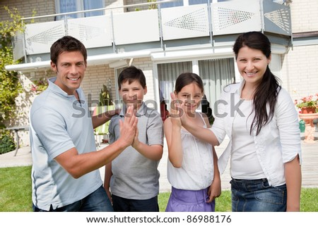 Portrait of happy young family giving high five to each other - stock photo