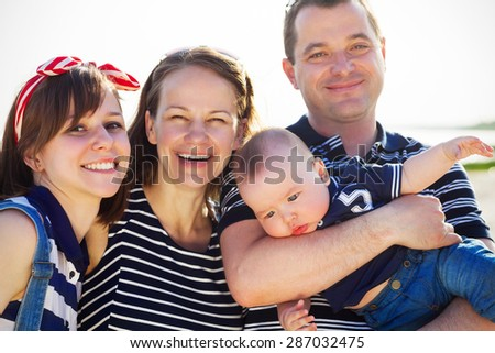 Portrait of happy young family having fun on the beach - stock photo