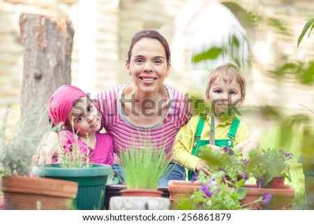 Portrait of happy young family in a garden - stock photo