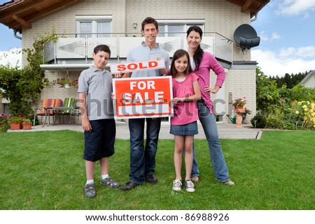 Portrait of happy young family in front of new home with sold real estate sign
