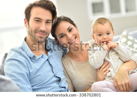 Portrait of happy young family of three - stock photo