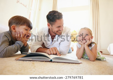 Portrait of happy young family of three lying on floor with a book. Father with two kids reading a story book in living room at home. - stock photo