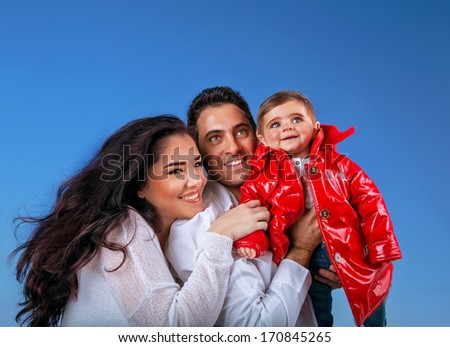 Portrait of happy young family on blue sky background, little girl with mother and father spending time together open air - stock photo