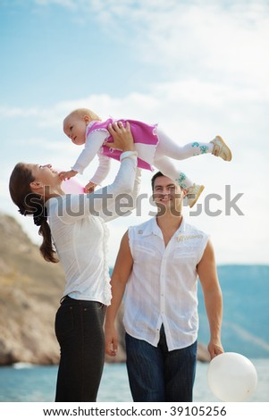 Portrait of happy young family playing with their child on berth near sea - stock photo