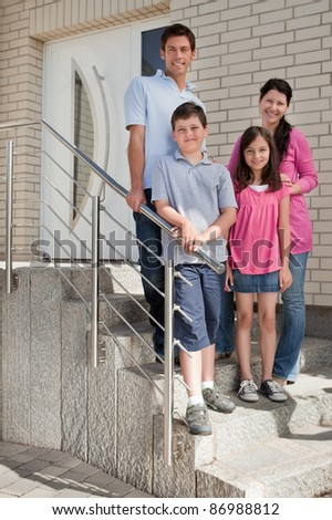 Portrait of happy young family standing at doorstep