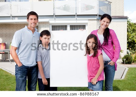 Portrait of happy young family standing outside with a blank sign board - stock photo