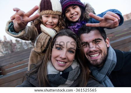 Portrait of happy young family taking a selfie in the street. - stock photo