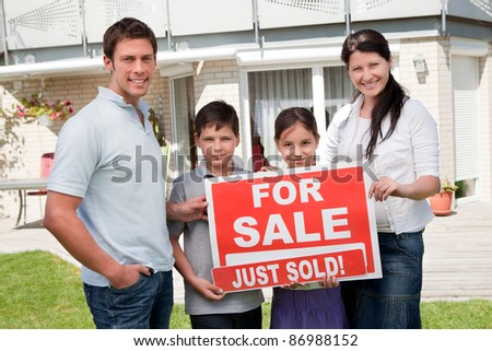 Portrait of happy young family with a sale sign outside their home - stock photo