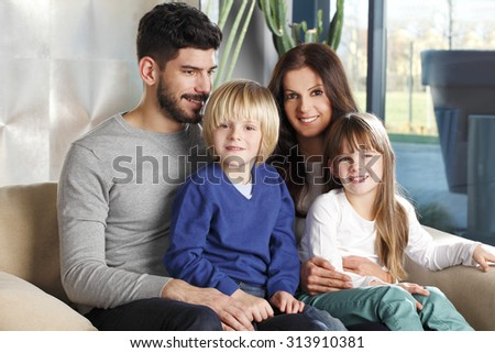 Portrait of happy young family with cute kids sitting at home on sofa.