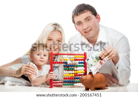 Portrait of happy young family with moneybox and accounting toy on white background - stock photo